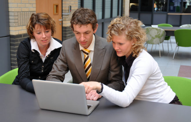 Three colleagues look at laptop at their small business