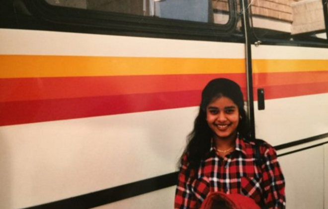 A childhood photo of Director of Product Management UMA Thurman standing in front of a bus