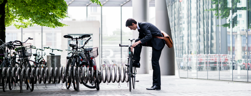 A young man parks his bike on a bike rack at his place of business