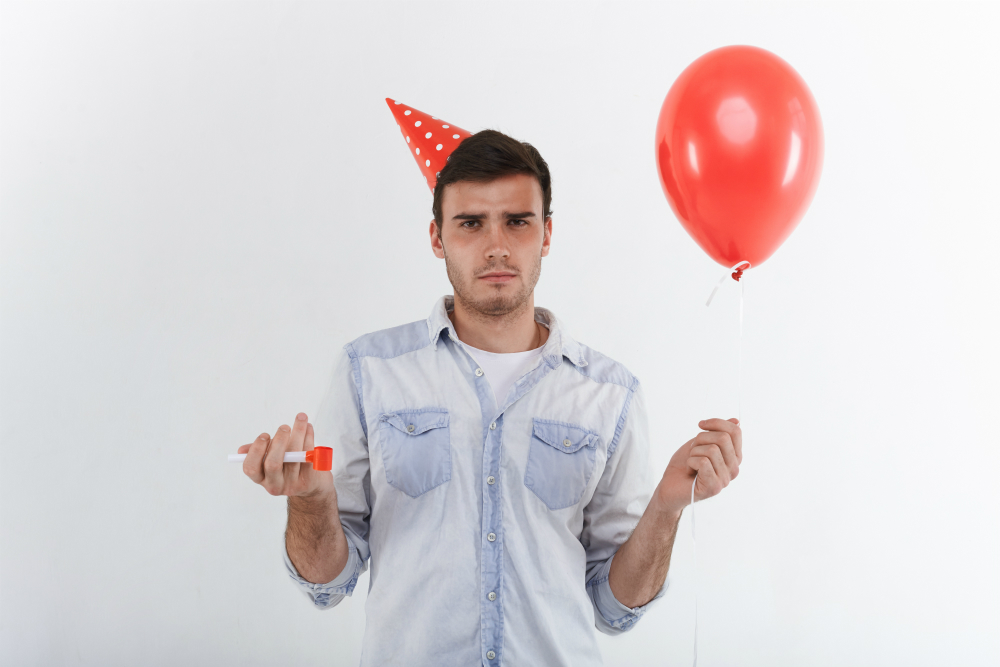 A young man looking confused holds a red balloon.