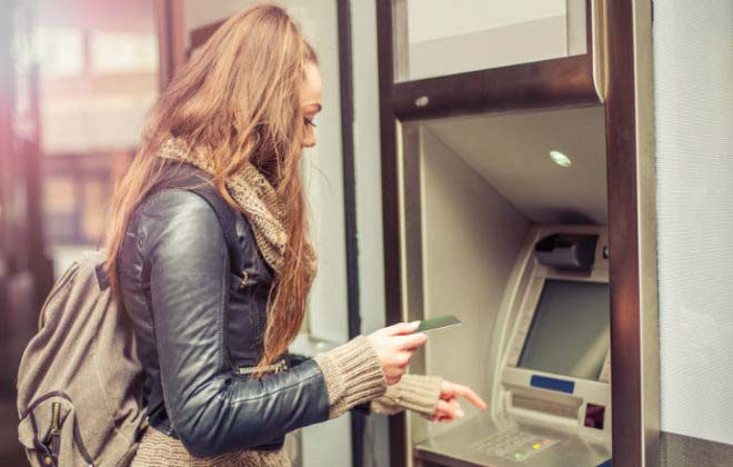 A woman uses ATM Crime Prevention tips to safely access her account.