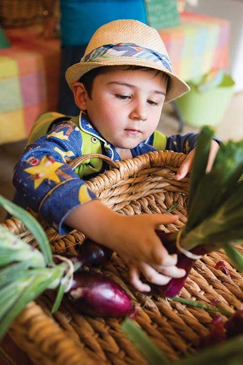A child selects a vegetable from the Denver Botanic Gardens veterans program