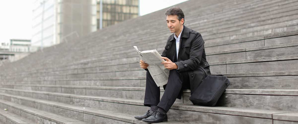 A man sat on stairs reading the UMB Monthly Media Update July 2019
