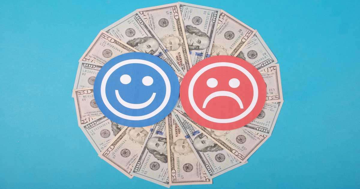 A smile and a frown symbolize the the emotions of money.