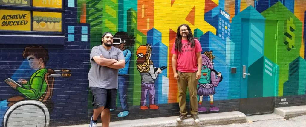 Artists JT Daniels and Phil Shaferpose in front of the murals outside of the School of Economics at UMB