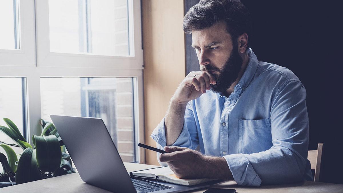 Man studies CARES act on laptop