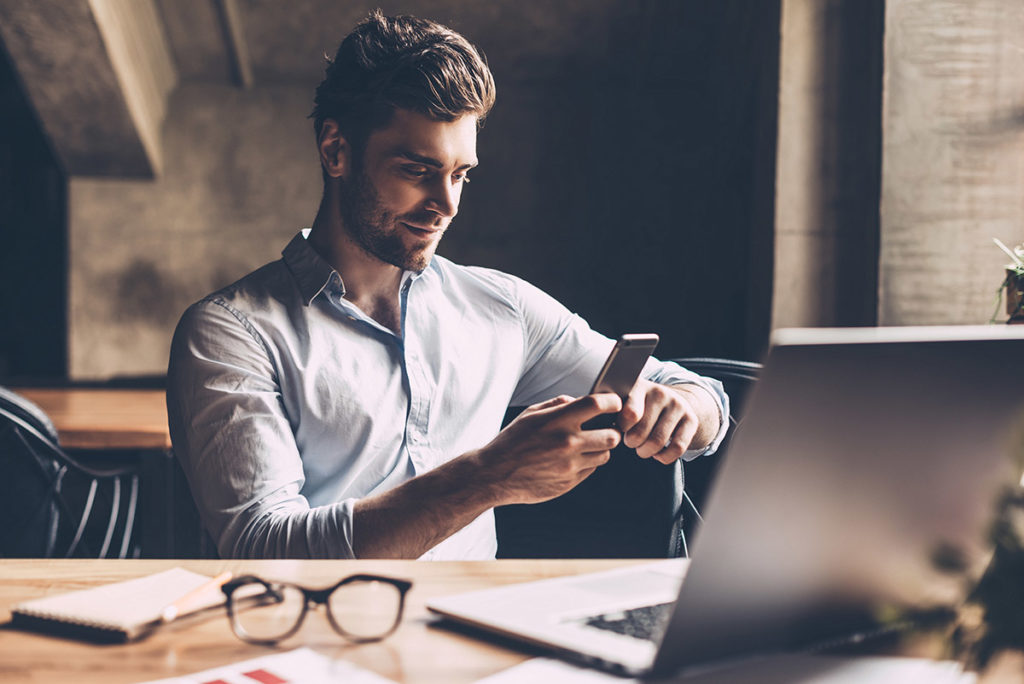 man managing debt at home desk