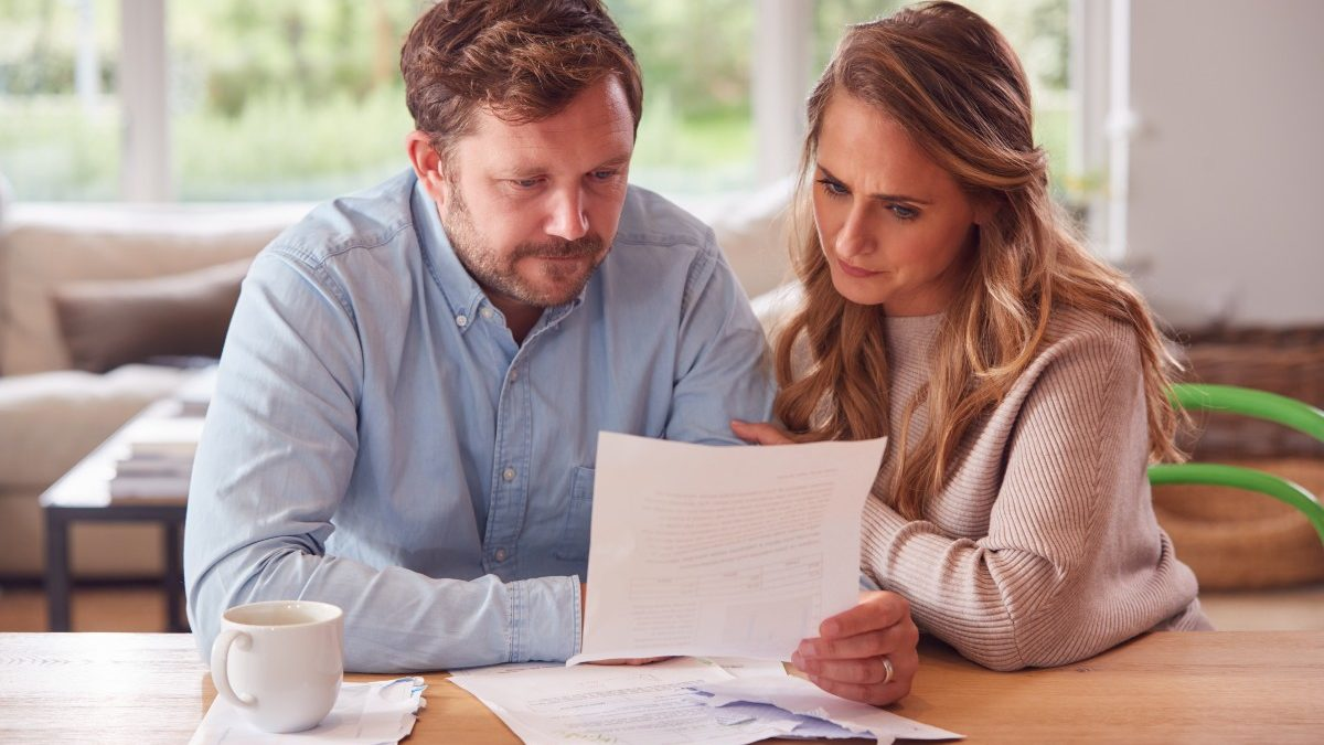 bigstock Worried Couple With Bills And 407283308 1
